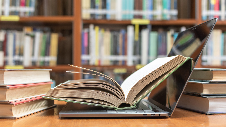 Libro aberto enriba dun portátil nunha biblioteca.