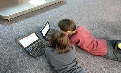 Dos niños delante de dos portátiles.