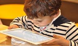 Neno mirando unha tablet.