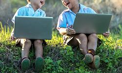 Dous nenos usando dous portátiles.