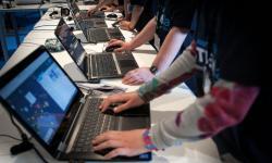 Varios jóvenes de pie delante de su respectivo portátil que están encima de una mesa.